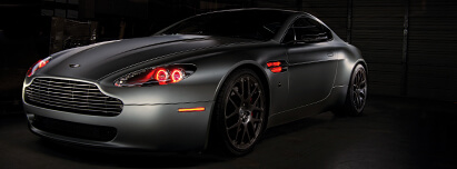 Flat grey Aston Martin with red halo headlights